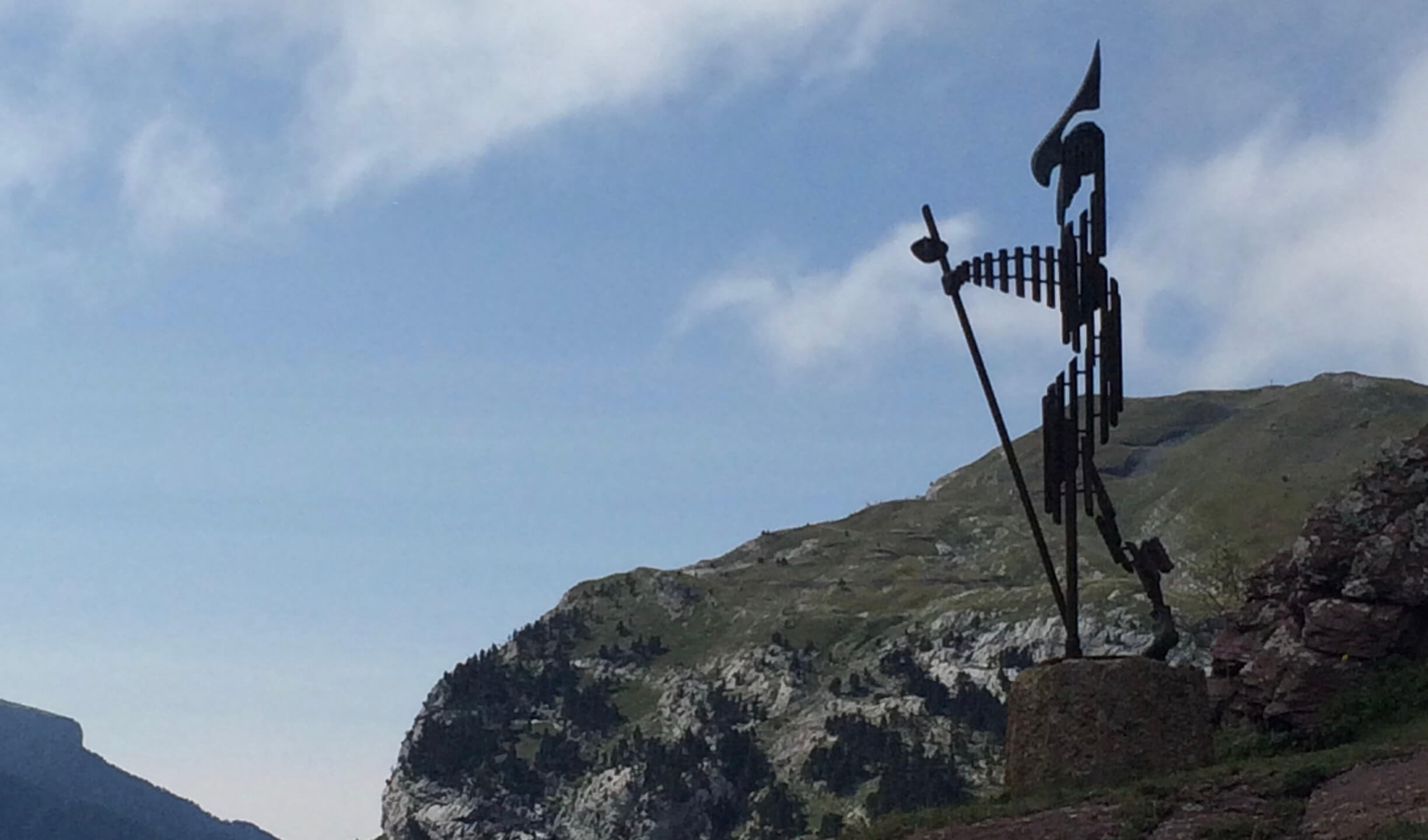 Sculpture of a pilgrim at Col du Somport with sky and mountains in the background